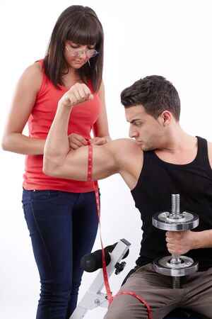 Pretty young woman measuring the biceps of handsome muscular man photo