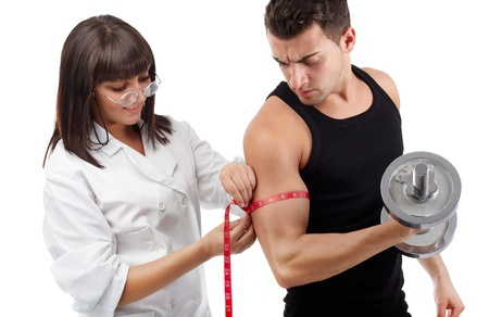 muscle woman: Pretty young nurse measuring the biceps of handsome man Stock Photo