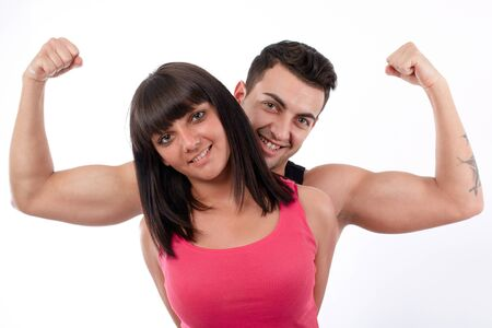 Young men showing his biceps behind a young women Stock Photo