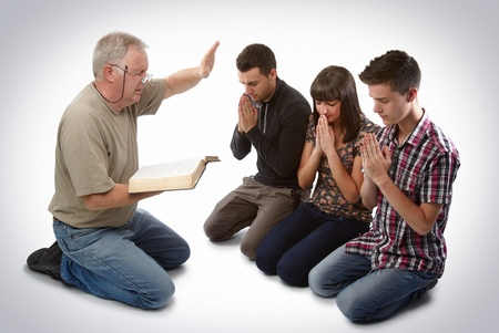 preacher: Preacher leading three young souls in prayer to receive Jesus Stock Photo