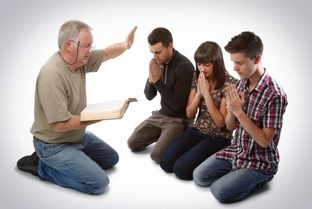 Preacher leading three young souls in prayer to receive Jesus Archivio Fotografico
