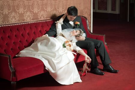 Bride and groom looking at each other on a sofa Stock Photo