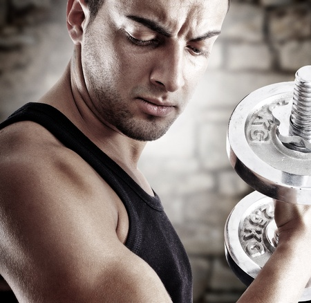 Young man doing weights lifting on stone background photo