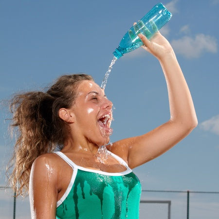 Young woman splashing herself with water to cool herself