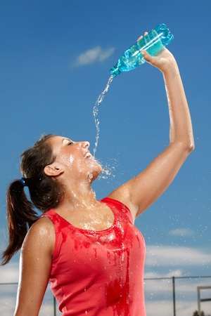 Young woman splashing herself with water photo