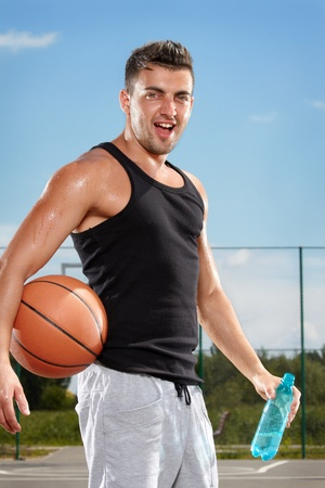 Thirsty basketball player drinking water on sports field photo