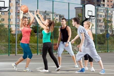 panier basketball: Jeunes hommes et femmes jouer au basket-ball dans un parc.