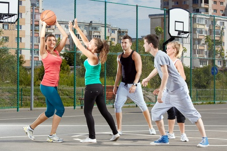 Young men and women playing basketball in a park photo