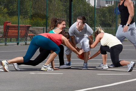 Young people playing basketball in a park