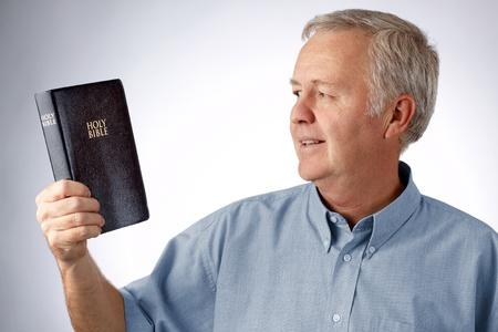 Uomo che guarda alla Bibbia in mano Archivio Fotografico - 10613271