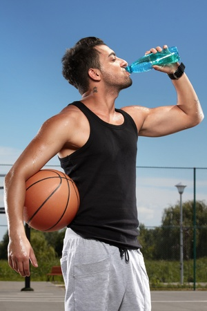 Young man drinking mineral water on a basketball court photo
