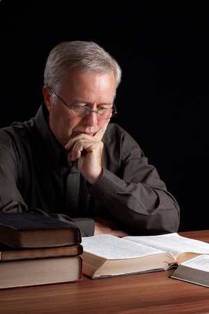 Senior pastor meditating and searching guidance photo