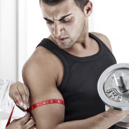 Nurse measuring the biceps of handsome man photo