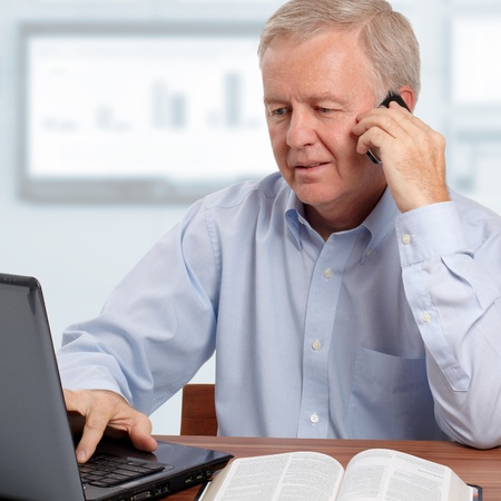 Man talking on phone in front of the laptop and the Bible