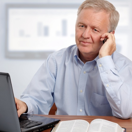 Man talking on phone and smiling in front of the laptop and the Bible photo
