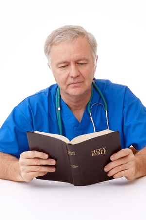 Surgeon man reading the Bible in working break Archivio Fotografico