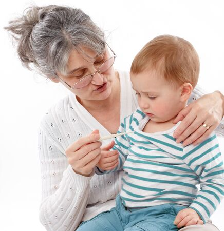 Granny holds grandson and checks his temperature photo