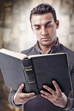 Portrait of a young man reading the Holy Bible photo