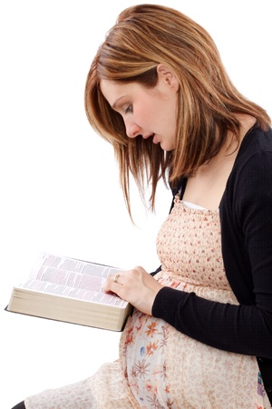 Young pregnant christian mother reading Bible for feeding her soul photo