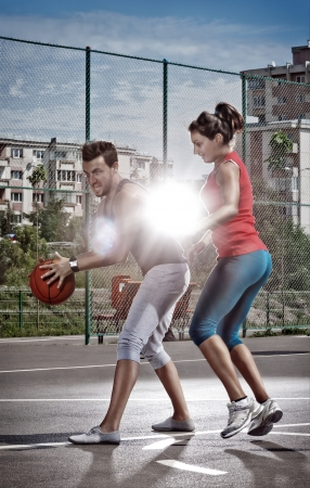 Young man and woman playing basketball on the playground photo