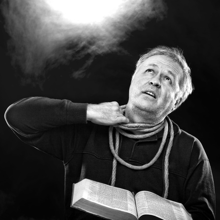 Man with Bible and trying to untie the rope from his neck (O Jerusalem: loose thyself from the bands of thy neck, O captive daughter of Zion.) Stock Photo - 12534376