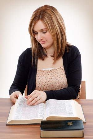 Young christian woman turning pages of the Bible searching for promises Archivio Fotografico