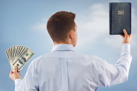 Young man choosing between God and money photo