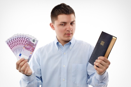 keeping: Young man with Bible looking on the euro banknotes.  Stock Photo