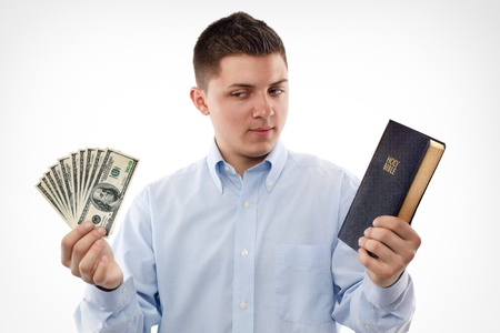 keep: Young man with Bible looking on the dollar banknotes.  Stock Photo