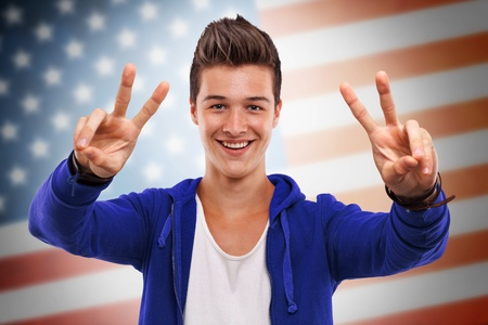 Portrait of a handsome young man gesturing victory symbol in front of US flag Stock Photo - 15398387