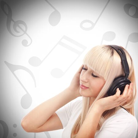 Pretty young girl enjoys listening music between musical notes photo
