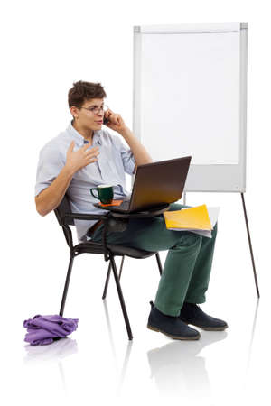 Young man with spectacles speaking on mobile and working on laptop in a workplace Stock Photo - 17414458