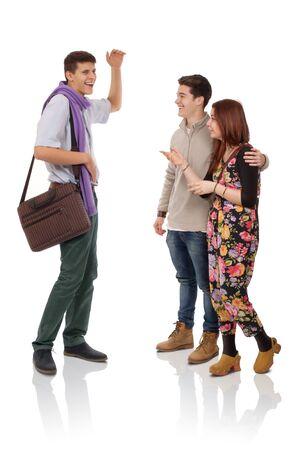 persona de pie: Tres jóvenes que discuten sobre algo divertido Foto de archivo