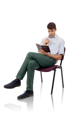 sitting on: Young christian man sitting and reading Holy Bible Stock Photo