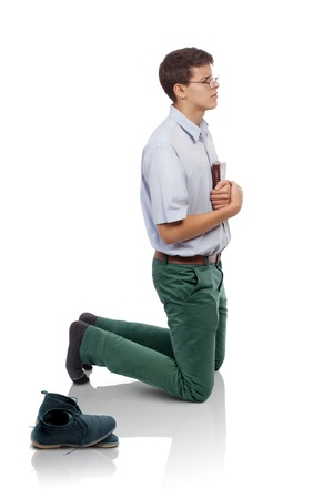 Young man humble knelt for prayer with the Bible in hands and a pair of shoes behind. (Concept for humble prayer time or holy place in my life.) Stock Photo - 17643297