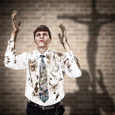 arrepentimiento: Hombre joven que viene a la cruz de Jesús con las manos sucias y la ropa