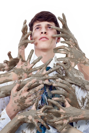 Young man looking up stained by multitude of dirty hands Stock Photo