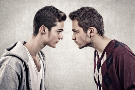 Two young angry people standing face to face photo