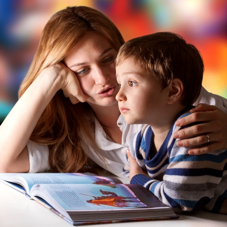 narrate: Little boy listening to his mother telling him stories Stock Photo