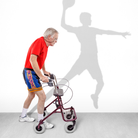Sick old man walking with a walker along with a shadow of a young athlete on the wall. Concept for youth passing like a shadow or hope for health rehabilitation. photo