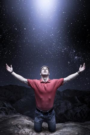 El hombre joven se arrodilló delante de una luz del cielo