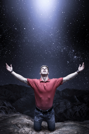 kneeling man: Young man knelt before a light from the sky