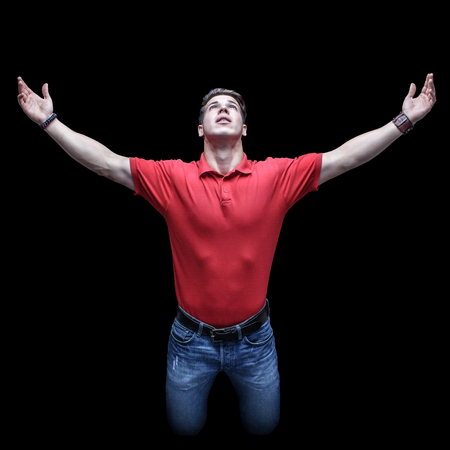 Young man looking up in a kneeling position with raised hands