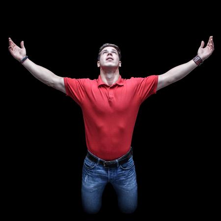 manos levantadas: Joven mirando hacia arriba en una posición de rodillas con las manos levantadas