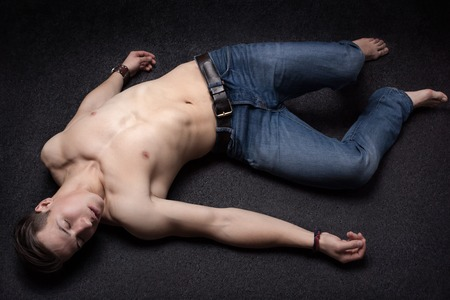 lay down: Young sportsman lying down unconsciously on apparent asphalt floor