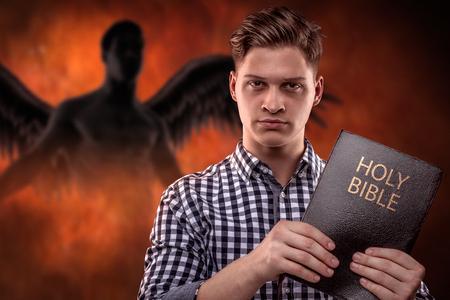 mano de dios: Hombre joven cristiano la celebración de una Biblia con un diablo en el fondo (concepto contra la tentación por la Palabra de Dios)