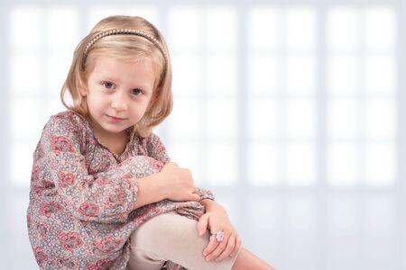 girl legs: Cute little girl sitting in front of windows Stock Photo