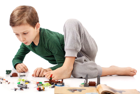 boy beautiful: Handsome guy who is playing and building something from book Stock Photo