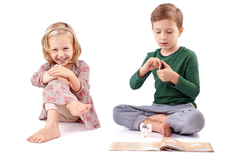 toddler boy: Boy and girl playing differently with different attitudes Stock Photo