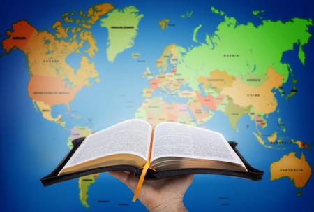 Mano mostrando la Sacra Bibbia contro mappa del mondo